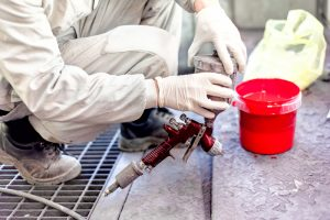 Industrial worker preparing red paint for spraying a car in painting booth