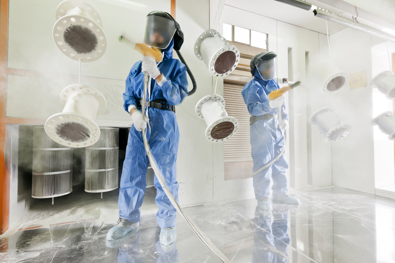 Worker wearing protective wear performing powder coating of metal details in a special industrial products