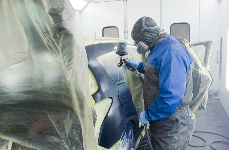 Professional at work, spraying a car